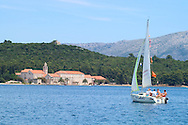 A group of people on a sailboat in front of the<br /> Franciscan Church and Monastery on the island of<br /> Badija on the Dalmatian Coast of Croatia<br /> c. Ellen Rooney