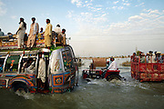 People travel through the flooded village of Sultan Kot, in Sindh Province, Pakistan.