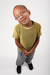 Young boy standing with head tilted to the side,