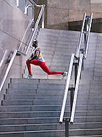 Male athlete stretching on staircase outside building