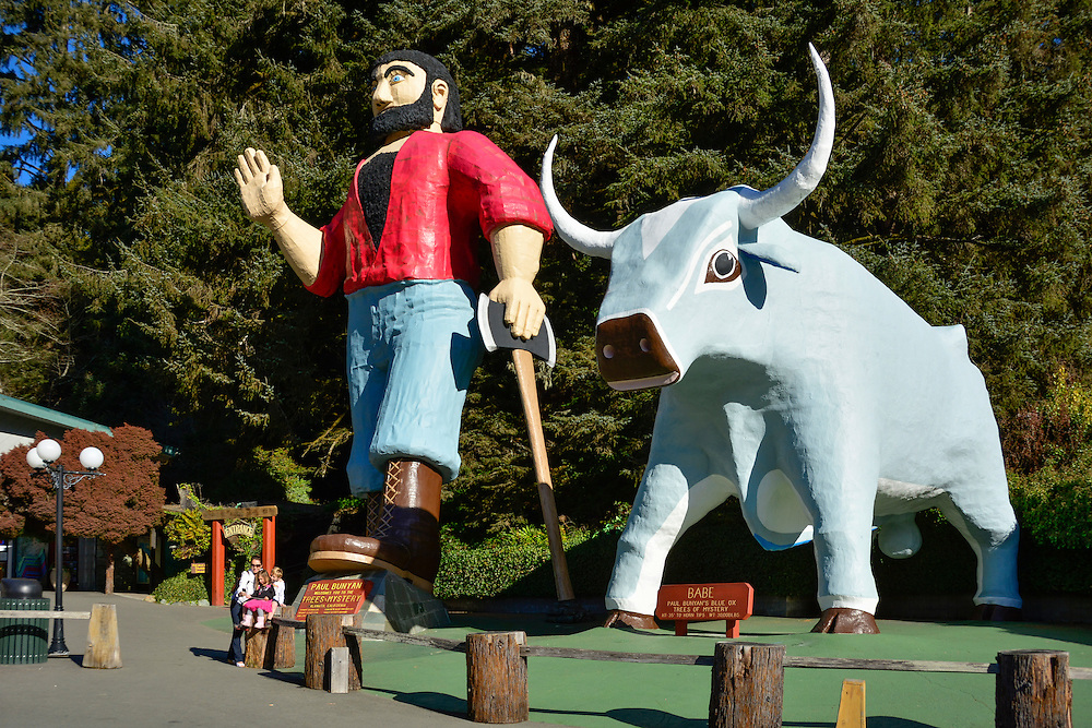 Family taking selfie with statues of Paul Bunyan and his ox Babe at Trees of Mystery in the Redwoods of northern California.