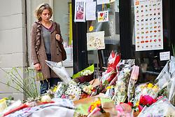 © Licensed to London News Pictures. 17/11/2015. Paris, France. Mourners visit a memorial outside La Belle Équipe cafe in Paris, France following the Paris terror attacks on Tuesday, 17 November 2015. Photo credit: Tolga Akmen/LNP