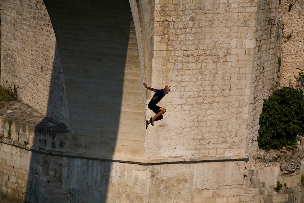 "Adem Mocca Pajevic jumps from the Old Bridge...Divers and tourists at Mostar's famous Old Bridge (Stari Most) in Bosnia and Herzegovina. This bridge is the city and region's biggest tourist attraction and there are busses full of tourists coming in from Sarajevo and Dubrovnik, Croatia. For 25euros tourists can train to jump from the bridge themselves, under supervision from the ""professional"" Mostar divers known as the Mostari. .."