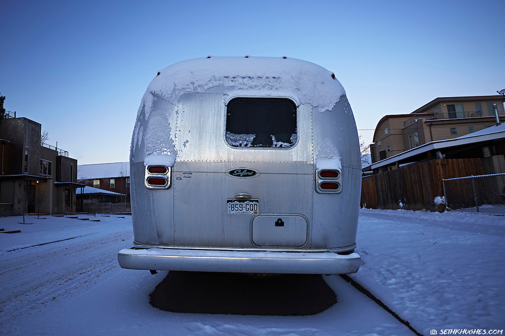 An Airstream trailer sits parked covered in snow and ice on a cold residential street in Denver, Colorado.