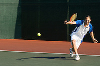 Tennis Player squatting on tennis court Hitting Backhand