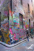 Young artist puts the finishing touches to his contribution to the ever-changing graffiti art in Hosier Lane, Melbourne, Australia