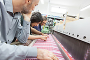 Soveria Mannelli (CZ) - Lanificio Leo. I designer dello Studiocharlie (Rovato - BS) controllano un diverse prove di tessiture realizzate su un telaio elettronico a pinze con licci.