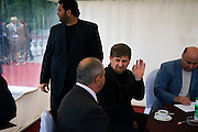 "Chechen President Ramzan Kadyrov talks attends a horse race in Moscow's Hippodrome. While he talks to another guest, his bodyguard looks out of the VIP tent. .Kadyrov's horse, ""Royal Quiet"", came first in the 1600-metre race. .The horse, born in the U.S.A., is parented by father: Real Quiet, mother: Dinasoar, is trained by S. G. Kolesnikov and rode by master jockey S. V. Petin.."