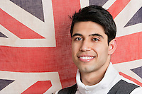 Portrait of patriotic young man with British flag in background
