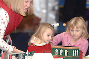 Mallory Rhem (left) speaks to her daughter Shannon (center) as she and Caitlynn Gehrett (right) enjoy one of the displays at the 2009 Festival of Trains at the Grand Traverse Heritage Center on Traverse City, Michigan.