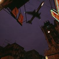 China, Hong Kong, Jet flies over crowded Kowloon streets at dusk