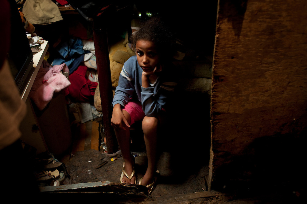 A young girl in the room she shares with two siblings. The floor is mud. Favela São Rafael, Guarulhos, Brazil.