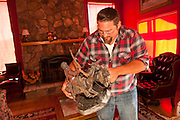 "04 JUNE 2011 - GREER, AZ: Robb Tyler (CQ 2 bb in Robb) packs up a piece of western art in his home in Greer. Tyler said more than 5 generations of his family have been coming to Greer and this is the first time they've had to evacuate because of a fire. The fire grew to more than 140,000 acres early Saturday with zero containment. A ""Type I"" incident command team has taken command of the fire.   PHOTO BY JACK KURTZ"