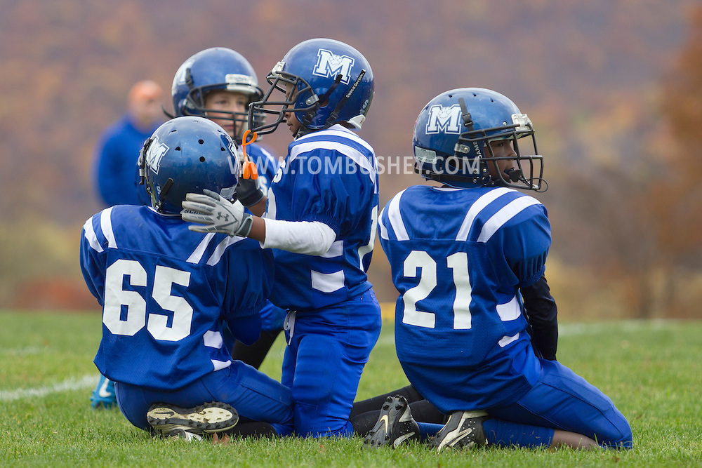 Salisbury Mills, New York  - Middletown players kneel on the field during a break in an Orange County Youth Football League Division I playoff game at Lasser Field on Sunday, Nov. 3, 2013.