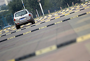 JINAN, CHINA - SEPTEMBER 22: (CHINA OUT) <br /> <br /> Intensive Deceleration Strips<br /> <br /> A car passes by intensive deceleration strips installed at north square of Jinan Sports Center on September 22, 2014 in Jinan, Shandong province of China. 10 deceleration strips with only 10 meter intervals between two latest strips are put on a road less than 200 meters at north square of Jinan Sports Center. The installment of deceleration strips near fitness facilities is to prevent fasting vehicles from breaking citizens. <br /> ©Exclusivepix