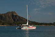 A sailboat sails past Diamond Head Crater on Oahu, Hawaii.