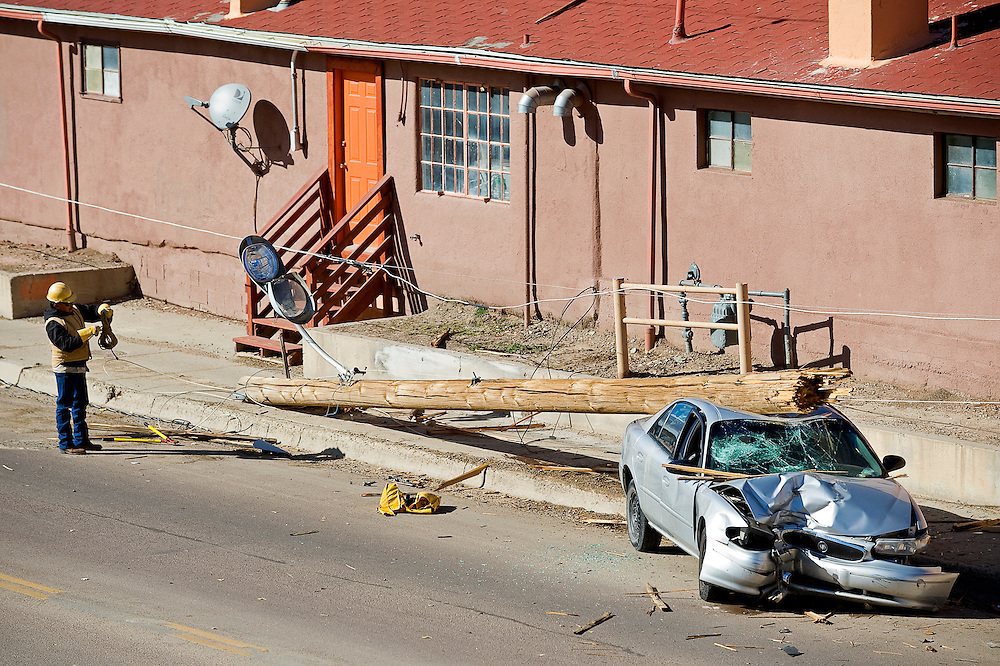 110910    Brian Leddy.A City of Gallup worker helps clean up at the scene of an accident on Aztec Avenue at the corner of Valley View Road on Tuesday afternoon. A juvenile driving the vehicle hit the telephone pole causing it to collapse on his vehicle.