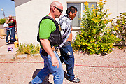 21 SEPTEMBER 2010 - PHOENIX, AZ:  Detective Cory Geffre (CQ) escorts a man arrested on an outstanding felony warrant to a waiting car. Crime has steadily dropped in Phoenix over the past few years, in line with national trends. The latest number released this month showed Phoenix reported fewer 2010 homicides, rapes, robberies, thefts - in addition to other major crimes -- compared with the same time period the previous year. Detectives in the Phoenix police department's Major Offender Unit make several arrests every day. PHOTO BY JACK KURTZ