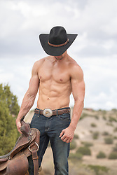Shirtless cowboy on a ranch with a saddle