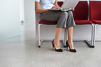 Woman using laptop on chairs in corridor low section