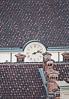 View across to the rooftops of Milan and to a clock, from the roof of the Duomo Cathedral,  Milan, Italy.
