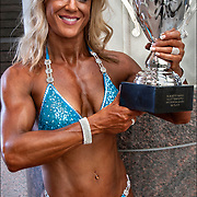 Marnie Hards smiling and holding one of her trophies for Women's 5th Figure Novice and 3rd Figure masters.<br /> <br /> In competitive amateur and professional bodybuilding, bodybuilders appear in lineups doing specified poses, and later perform individual posing routines, for a panel of judges who rank competitors based on criteria such as muscularity and conditioning.