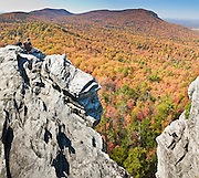 From atop Hanging Rock, you can view across a sea of autumn orange and red foliage to Moore's Wall, at Hanging Rock State Park in Stokes County, North Carolina, USA. (Panorama stitched from 2 images.) The eroded quartzite knob called Hanging Rock rises to 2150 feet elevation. The park is 30 miles (48 km) north of Winston-Salem, and approximately 2 miles (3.2 km) from Danbury. Hanging Rock State Park is located in the Sauratown Mountain Range, which is made up of monadnocks (or inselbergs, isolated hills) that are separated from the nearby Blue Ridge Mountains. Prominent peaks in the Sauratown range rise from 1,700 feet (520 m) to more than 2,500 feet (760 m) in elevation and stand in contrast to the surrounding countryside, which averages only 800 feet (240 m) in elevation. Named for the Saura Native Americans who were early inhabitants of the region, the Sauratown Mountains are the erosion-resistant quartzite remnants of mountains pushed up between 250 and 500 million years ago. Stitched from 3 overlapping photos.