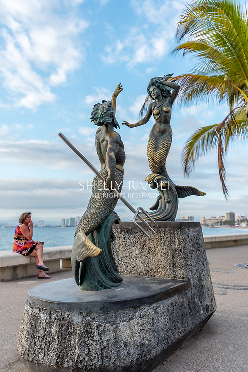 Sculpture of Triton and Mermaid by Carlos Espino (Neptune and the Nereid) on the Puerto Vallarta Malecon w/ woman smoking in background wearing colorful dress