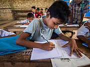 06 NOVEMBER 2014 - SITTWE, RAKHINE, MYANMAR: A boy in a school for Rohingya IDPs works on an assignment in his classroom. After sectarian violence devastated Rohingya communities and left hundreds of Rohingya dead in 2012, the government of Myanmar forced more than 140,000 Rohingya Muslims who used to live in and around Sittwe, Myanmar, into squalid Internal Displaced Persons camps. The government says the Rohingya are not Burmese citizens, that they are illegal immigrants from Bangladesh. The Bangladesh government says the Rohingya are Burmese and the Rohingya insist that they have lived in Burma for generations. The camps are about 20 minutes from Sittwe but the Rohingya who live in the camps are not allowed to leave without government permission. They are not allowed to work outside the camps, they are not allowed to go to Sittwe to use the hospital, go to school or do business. The camps have no electricity. Water is delivered through community wells. There are small schools funded by NOGs in the camps and a few private clinics but medical care is costly and not reliable.   PHOTO BY JACK KURTZ