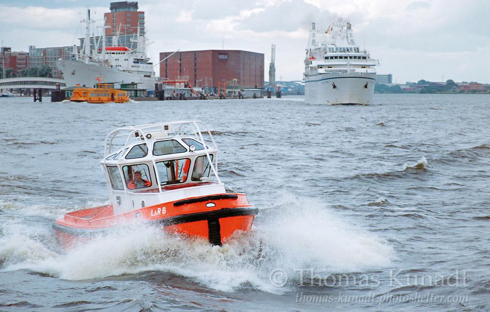 Festmacherboot L&R 6 in voller Fahrt auf der Elbe vor der CAP SAN DIEGO und dem Kreuzfahrtschiff SONG OF FLOWER am 22.07.2002, im Hintergrund der Kaispeicher A, auf dem die Elbphilharmonie entstehen wird.
