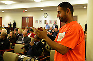 Feb. 25, 2013 - Mineola, New York, U.S. - CARLOS ENCARNACiON (in orange shirt) from the New York Communities for Change organization, of Hempstead, attends Nassau County Legislature meeting to show he is against the controversial Redistricting Map proposed by Republicans. The legislature postponed the vote on the map shortly before 1 AM the morning of February 26, nearly 12 hours after the meeting started on 1:30 PM Feb. 25. The meeting was so well attended that some visitors had to stand in the chambers or watch in other rooms of the legislative building.