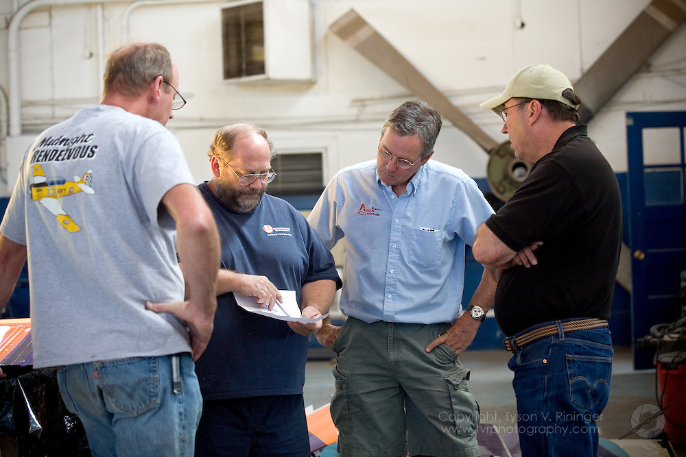 Rare Bear Preparation 2009. (L-R) Mechanics Keith Geary and Rob Grosvenor discuss aircraft modifications with Team Lead Alby Redick and Crew Chief Dave Cornell.