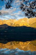 Early AM sun lights the  high peaks of the Southern Alps creating mirror-like reflections on Lake Wakatipu near Glenorchy in New Zealand's South Island.