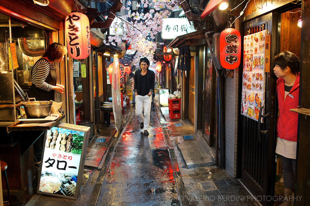 A young man walks through the restaurants of Omoide Yokocho (?????). The name of this tiny street, close to Shinjuku station in Tokyo, means Memory Lane because the area has remained unchanged since the times it was rebuilt after the bombing of the Second World War.<br /> If you wonder how post war Japan looked like this is your best spot. Japan.