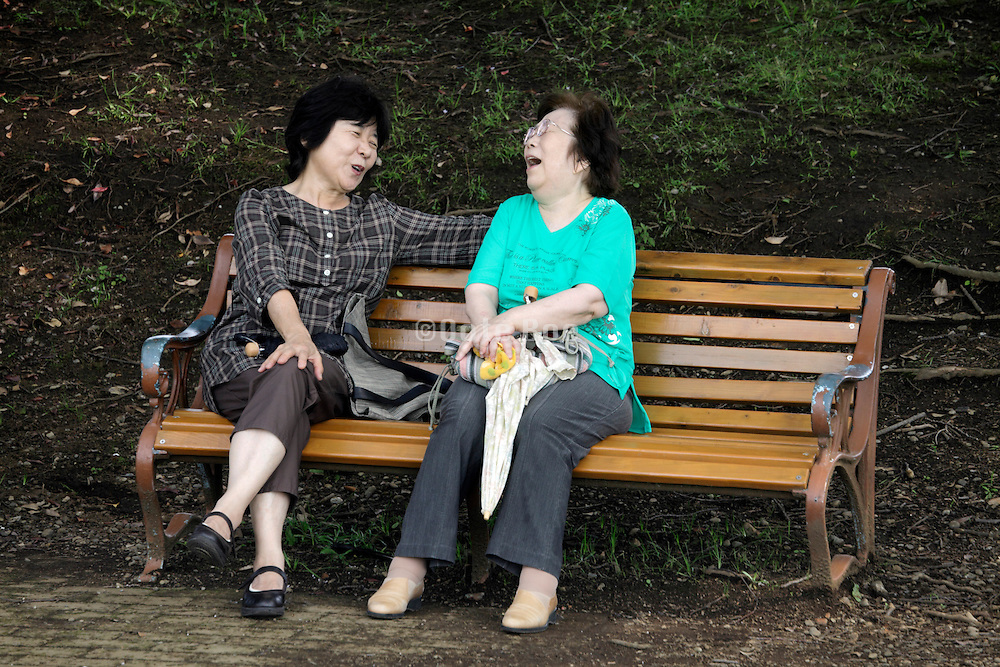 two woman on a park bench having a great time chatting