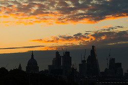 © Licensed to London News Pictures. 11/08/2017. LONDON, UK.  The sun rises behind clouds and St Paul's Cathedral and skyscrapers this morning. The capital has seen a cold start to day following a spell of wet weather this summer. Photo credit: Vickie Flores/LNP
