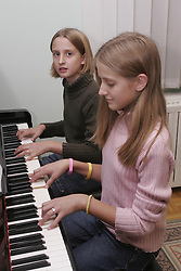 Two girls playing a piano. (Photo by Vid Ponikvar / Sportida)