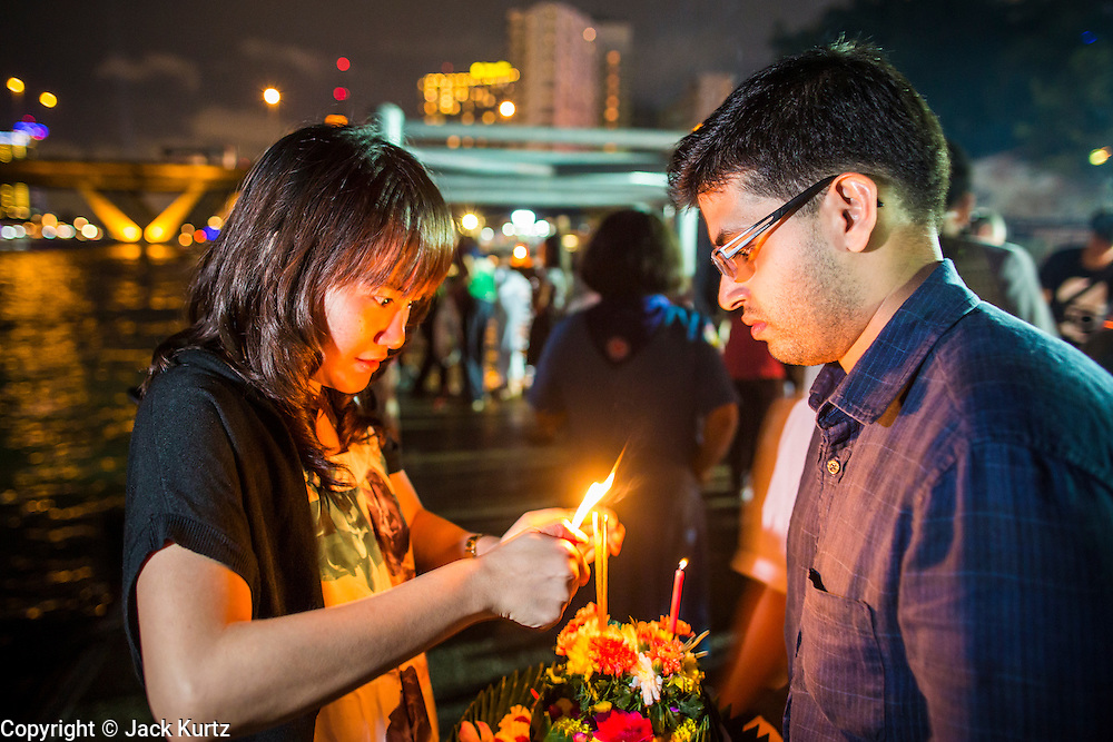 28 NOVEMBER 2012 - BANGKOK, THAILAND: A couple lights the candles and incense on their krathong before putting it in the Chao Phraya River for Loy Krathong at Wat Yannawa in Bangkok. Loy Krathong takes place on the evening of the full moon of the 12th month in the traditional Thai lunar calendar. In the western calendar this usually falls in November. Loy means 'to float', while krathong refers to the usually lotus-shaped container which floats on the water. Traditional krathongs are made of the layers of the trunk of a banana tree or a spider lily plant. Now, many people use krathongs of baked bread which disintegrate in the water and feed the fish. A krathong is decorated with elaborately folded banana leaves, incense sticks, and a candle. A small coin is sometimes included as an offering to the river spirits. On the night of the full moon, Thais launch their krathong on a river, canal or a pond, making a wish as they do so.    PHOTO BY JACK KURTZ