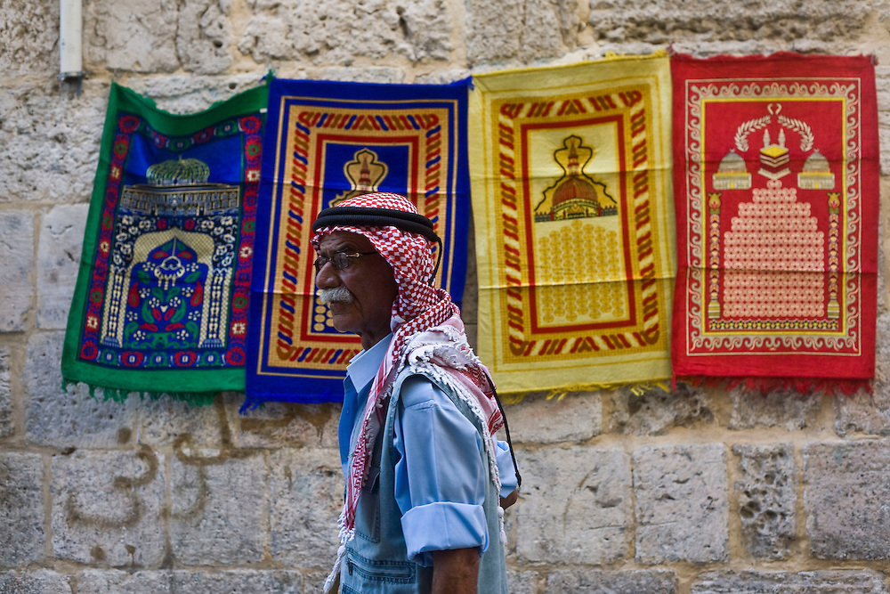 A Palestinian Muslim walks past prayer rugs hanged for sale on a wall in the Old City of Jerusalem, on his way to attend the first Friday prayers of the holy month of Ramadan, Friday Aug. 28, 2009. Muslims throughout the world are celebrating the holy month of Ramadan, where observants fast from dawn till dusk...Photo by Olivier Fitoussi /ABACAUSA.COM