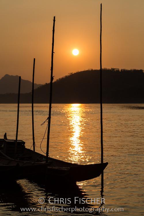Traditional boats docked to bamboo poles in the Mekong River at sunset, Luang Prabang, Laos.