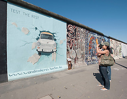 Tourists photographing paintings on Berlin Wall at East Side Gallery in Berlin Germany