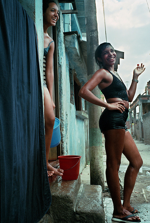 "Women in the favelas after having had an afternoon shower to cool down from the relentless heat. 'The media here tend to portray all the favelados as heavily armed drug dealers"", declares Luke, an Englishman who set up a local boxing gym to help local chldren. ""The truth is that only two or three percent of people are involved in drug-trafficking. The rest are just terribly poor people who suffer awfully"" Rio de Janerio, Brazil. 2001"