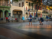 Boy doing a handstand while his coach watches, in the evening, on the the promenade, the Paseo del Prado, that divides Centro and Old Havana.