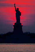 Sun sets directly behind Lady Liberty, as seen from Red Hook, Brooklyn.