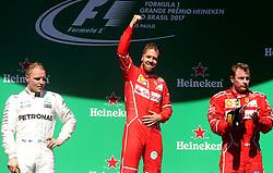 """SP - FÃ""""RMULA 1/GP DO BRASIL - ESPORTES -  O piloto alemão Sebastian Vettel (c), da Ferrari, comemora após vencer o Grande Prêmio   do Brasil de Fórmula 1, no Autódromo de Interlagos, na zona sul de São Paulo, na tarde   deste domingo (12). O finlandês Valtteri Bottas (E), da Mercedes, foi o segundo e, o   também finlandês Kimi Raikkonen, da Ferreri, o terceiro.   12/11/2017 - Foto: WERTHER SANTANA/ESTADÃO CONTEÚDO (Credit Image: © Agencia Estado/Xinhua via ZUMA Wire)"""