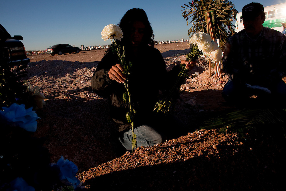 "A mother and father of a teenage victim decorate their sons grave on ""Day of the Dead"" in November."