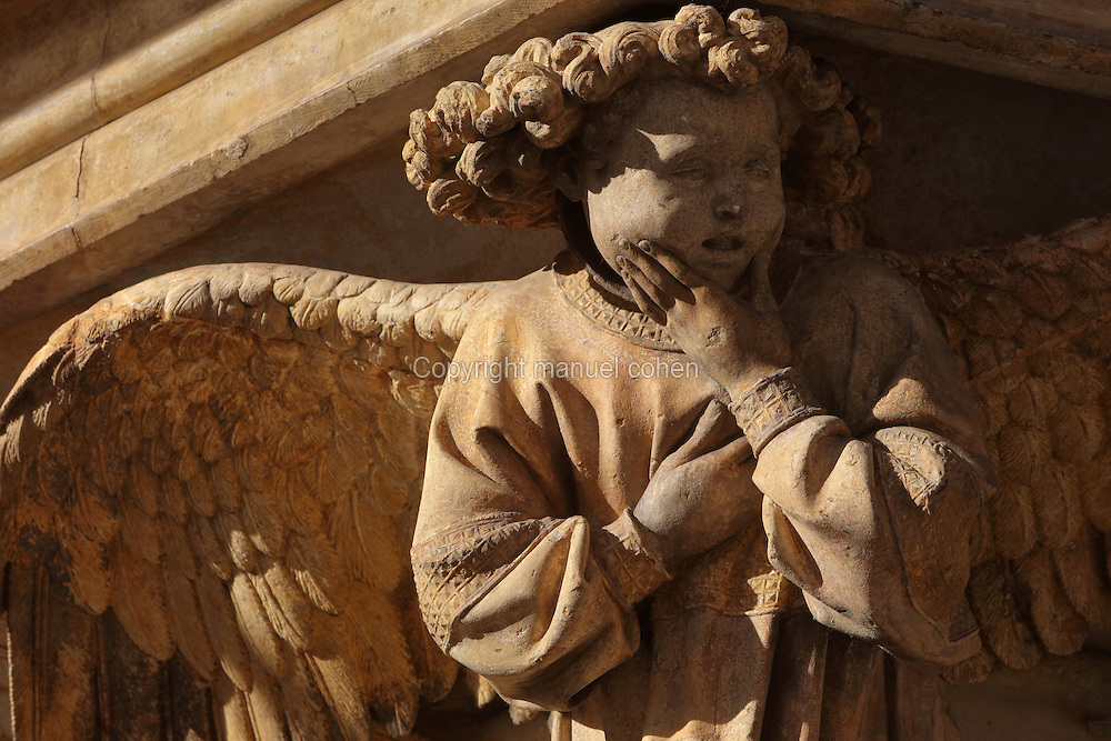 Weeping angel, one of six above columns between the prophets, from the Puits de Moise, or Well of Moses, 1395-1403, sculpted by Claus Sluter, 1340-1406, and his studio, and painted by Jean Malouel, 1365-1415, in the courtyard of the Chartreuse de Champmol, the burial site of Philippe le Hardi duc de Bourgogne, or Philip the Bold Duke of Burgundy, now the Hospital de la Chartreuse, Dijon, Burgundy, France. The angels serve to help the viewer understand the Passion of Christ. The sculpture was commissioned by Jean sans Peur or John the Fearless, and consists of a crucifixion scene surrounded by 6 prophets (Moses, David, Jeremiah, Zachariah, Daniel and Isaiah), with 6 weeping angels. The hexagonal building surrounding the sculpture was added in the 17th century. Picture by Manuel Cohen