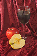 Apple and wine on a red velvet background