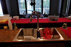 A kitchen counter top circa 1975 has an upgraded sink and faucet with a red pitcher setting in it.  On the counter is a plastic food keeper, a basket of sink stoppers, a ceramic frog that holds dishwashing objects, liquid soap, store bought cookies and a measuring cup