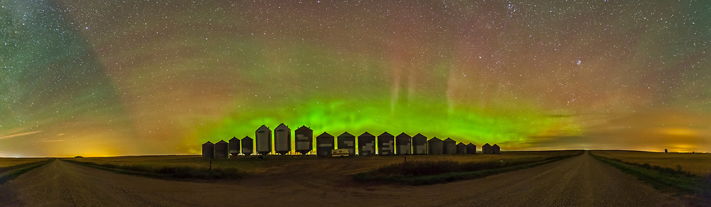 A 180° panorama of a modest aurora display behind grain bins on an Alberta country road. The aurora adds more color to a sky also filled with green airglow, while at the ends of the roads are yellow glows of light pollution, from Strathmore and Calgary at left, and Bassano at right. For a few minutes there was also the sharp edge at left to the aurora rays, present in 3 frames of the panorama, so it is not an artifact of the stitching. The Big Dipper is left of centre, low in the north.